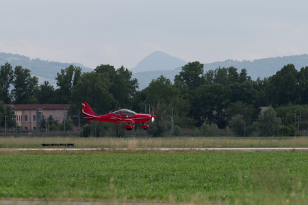 Small and Light Red Piper Aircraft Taking off from the Runway.