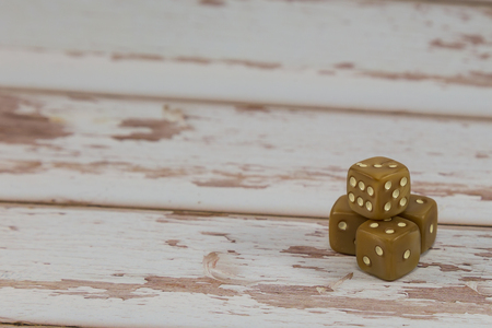 Plastic Dices on White Wooden Table: Gambling Theme.