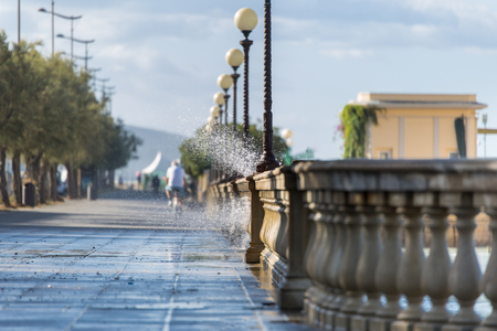 Sea Waves Passing Through the Parapet of a Sidewalk in Windy Day: Stormy Weather. Фото со стока