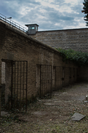 Unkempt Courtyard of an Old Prison Full of Weeds and Cells. Stock Photo
