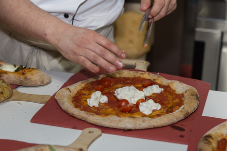 Pizza Maker who Prepares a Delicious Pizza with Cheese and  Cherry Tomatoes. Foto de archivo