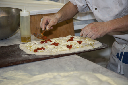 Processing of the Pizza Dough by the Pizza Maker. Foto de archivo