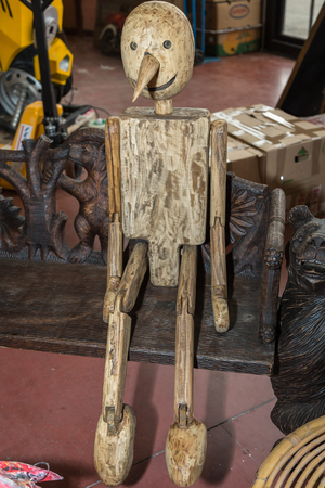 Wooden Articulated Puppet Sitting on a Bench.