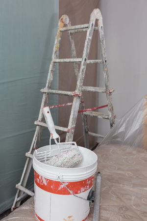 Staircase and Tools for Painting and Furniture with Transparent Protective Sheeting.