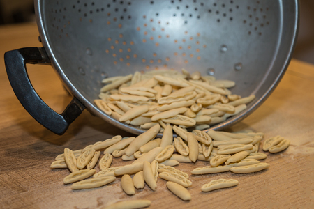 Short, Raw Dough-Pasta- coming out of a Strainer. Stock Photo