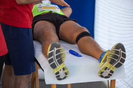 Athlete lying on a Bed while having Legs Massaged after a Physical Sports Workout.