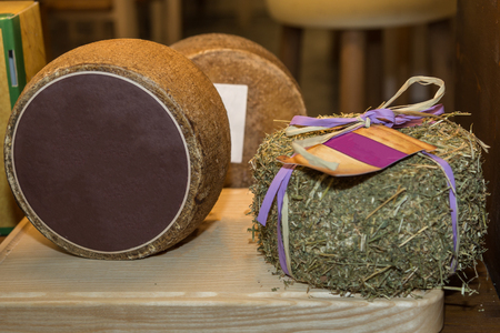 Cheese with Rind Covered with Hay on a Wooden Table.