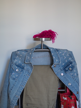 Jeans Jacket with White Beads and Beige Trousers Hanging on a Metal Coat Rack.