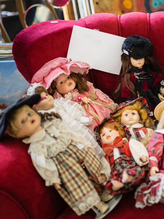 Group of Antique Dolls on a Red Couch.