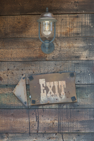Exit Sign and Arrow on Wooden Frame near Vintage Oil Lamp.