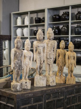 Six Buddhist Figurines with Inscriptions on a Table.