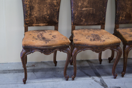 Worn Brown Vintage Leather and Wooden Chairs. Reklamní fotografie