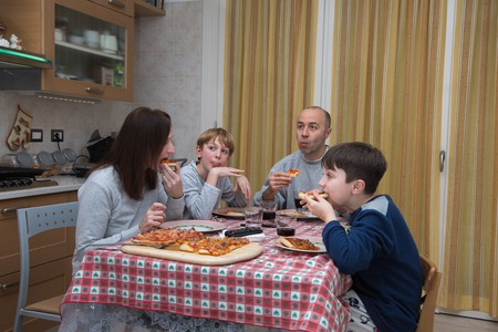 Family of Four People Eating Pizza on the Kitchen Table at Home.