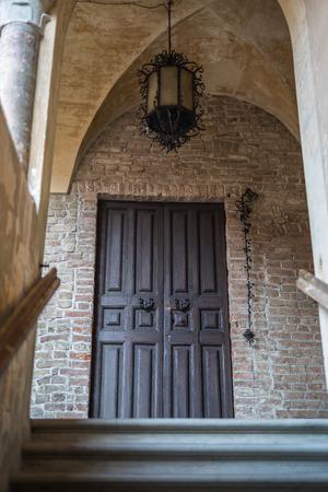 Antique Wooden Door with Antique Metal Chandelier in Fontanellato in Parma, Italy.