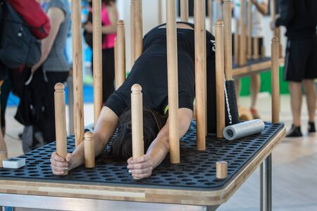 Girls doing Fitness Exercises on a Perforated Table with Movable Wooden Columns. Stock Photo