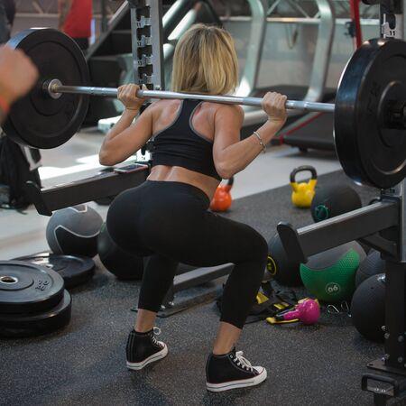 Fitness-Workout im Fitnessstudio: Frau macht Übungen im Outdoor-Kurs mit Langhantel und Gewichten.