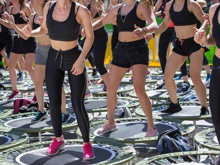 Mini Rebounder Workout - Ragazze che fanno esercizio di fitness in classe in palestra con musica e insegnante sul palco.