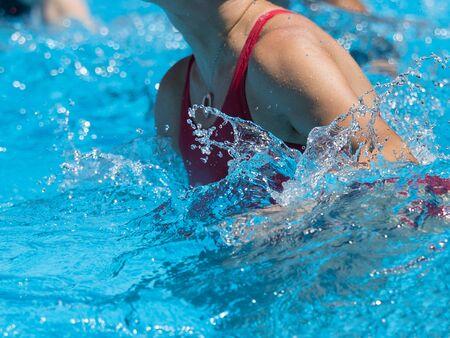 Mujer haciendo aeróbic acuático al aire libre en una piscina.