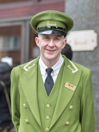 Street Photography: Portrait of Harrods Department Store Receptionist with Green Uniform and Hat in London.