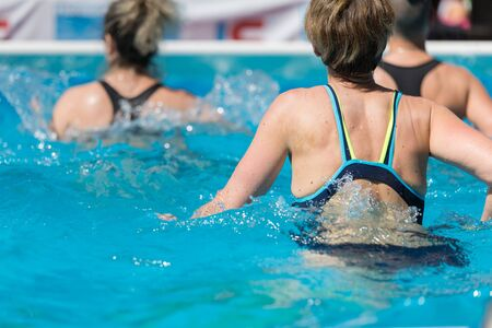 Woman Doing Water Aerobics Outdoor in a Swimming Pool. Reklamní fotografie