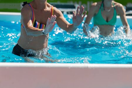 People Doing Water Aerobics Outdoor in a Swimming Pool.