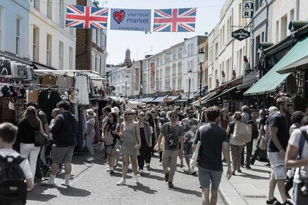 People Walking in Portobello Road in London in a Sunny Day.