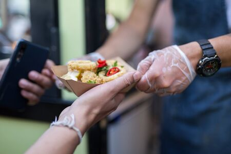 Street Food: Fried Fish, Squids Served in a Small Paperboard. Stock Photo