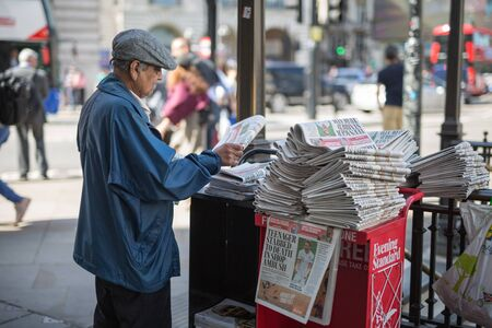 Street Photography: Elderly Newspaper Salesman with a hat in Londons Street. Stock Photo