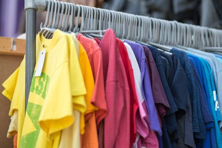 Group of Coloured T-shirts for Sale Hanging on a Garment Holder.