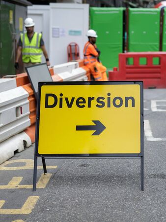 Yellow Road Sign with Arrow, Diversion: Barrier and Workers in background.