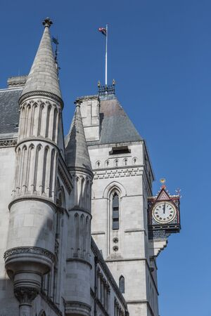 Shiny and Shining Golden Clock, detail of The Royal Courts of Justice Facade in London.