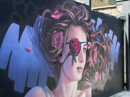 Graffito On The Wall: Portrait of a Beautiful Girl with Curls and Pink Bandage in the shape of a Rose on her Eye.