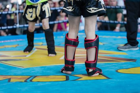 Children Fighting a Boxing Match: particular of their Legs with the Protections.