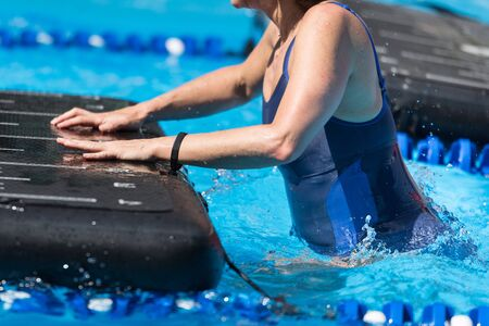 Girl Doing Exercises on Floating Fitness Mat in an Outdoor Swimming Pool.