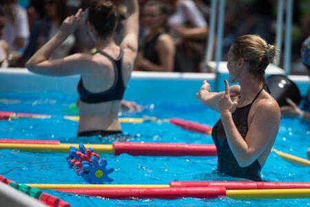 Women Doing Water Aerobics Outdoor in a Swimming Pool.