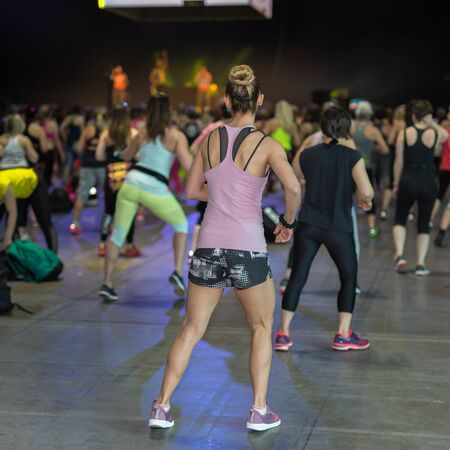 Fitness Workout in Gym: People doing Exercises in Class with Music and Teacher on Stage.