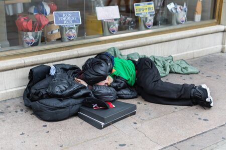 Street Photography: Homeless Sleeping on the Street in front of a Store Window.