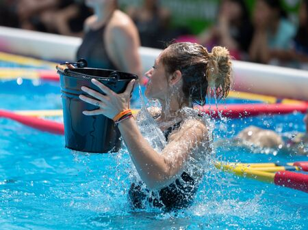Girl Doing Water Exercises in Outdoor Swimming Pool Emptying a Bucket of Water on her  Head.