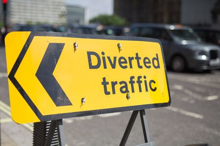 Yellow Road Sign with Arrow: Diverted Traffic.