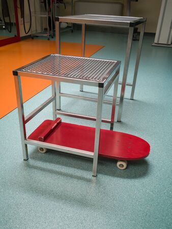 Metal Stool and Red Skateboard for Physiotherapy Use within a Medical Centre.