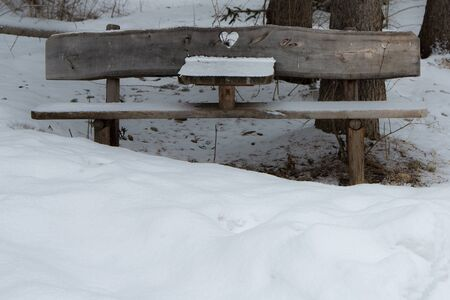 Wooden Bench with Heart Carved in wood Among Fresh Snow in Italian Dolomites Mountains. Foto de archivo