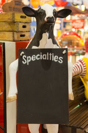 Empty Specialties Menu Chalkboard Supported by a Cow-Shaped Figure.