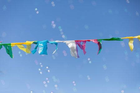 Colorful little Flags Moved by the Wind: Sky in the background and Soap Bubbles in the Air.