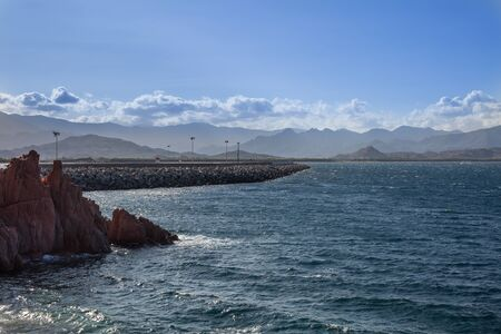 Sardinia Coastline: Rocks and Cliffs near Sea and Tourists; Italy.