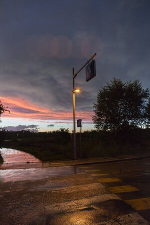 Dramatic Sky after a Storm, Vegetation in Backlight and Street in the Dark with Streetlights. Banque d'images