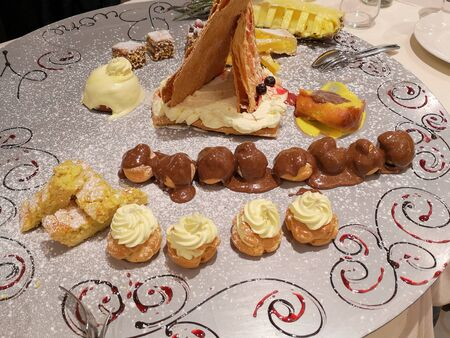 Chocolate Puffs, Cream Pastries and Various Sweets in a large Tray of Great Visual Impact.