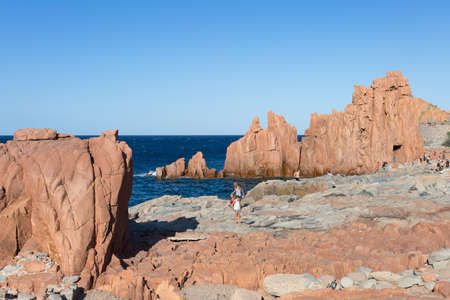 Sardinia Coastline: Typical Red Rocks and Cliffs and Tourists near Sea in Arbatax; Italy. Imagens