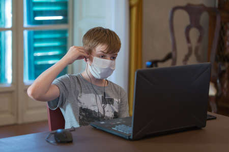 Boy with a White Surgical Mask and Headphones in front of a Laptop while Attending a Class at the Time of the Coronavirus.