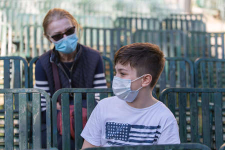 12-year-old Boy with a Surgical Mask Talking to a Lady with a Surgical Mask at the Time of the Coronavirus.