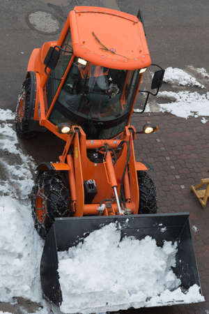 Orange-colored Snowplough Operating on the Road.